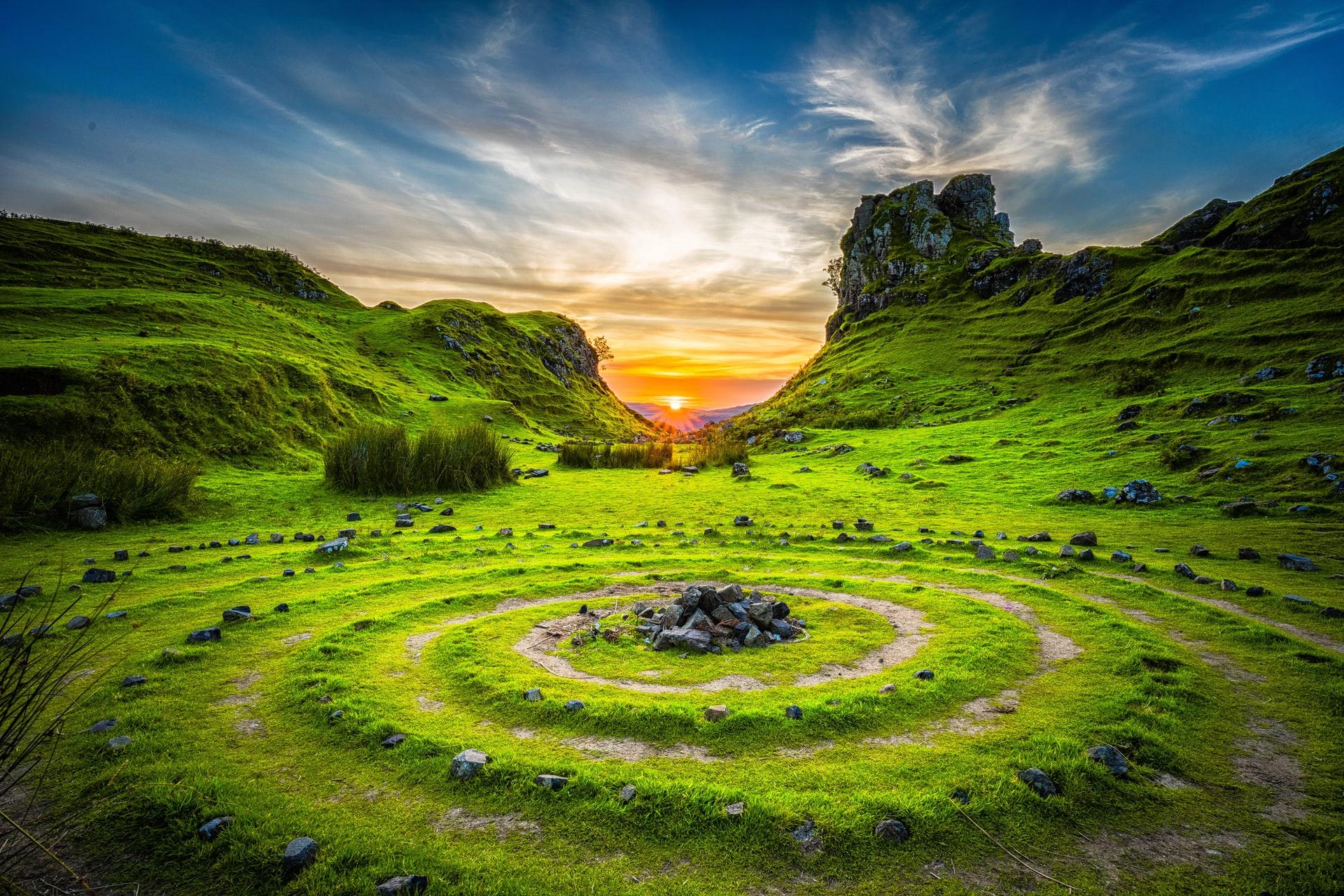 grüne Rasenkreise in Tal mit Sonnenaufgang in der Ferne