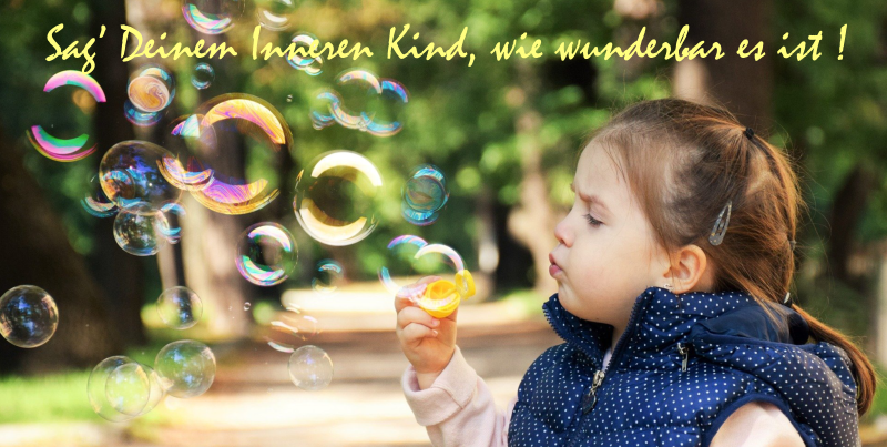 Mädchen mit Seifenblasen mit Spruch Sag Deinem Inneren Kinde, wie wunderbar es ist!